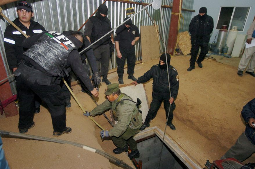 ** FILE ** This Jan. 25, 2006, file photo shows a Mexican federal police officer reaches down to assist a Mexican army soldier after climbing up a ladder from a sophisticated clandestine tunnel that passes under the U.S.-Mexico border in Tijuana, Mexico. (AP Photo/David Maung,File)