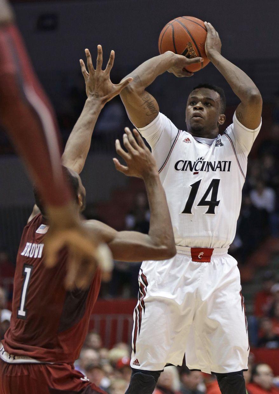 Cincinnati guard Ge'Lawn Guyn (14) shoots over Temple guard Josh Brown (1) during the first half of an NCAA college basketball game, Tuesday, Jan. 14, 2014, in Cincinnati. (AP Photo/Al Behrman)