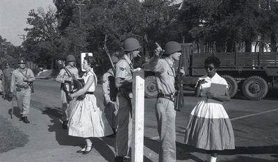 FILE - In this Sept. 4, 1957 file photo, Elizabeth Eckford, right, is turned away by Arkansas National Guardsmen as she approaches Little Rock Central High. The guardsmen were instructed by Gov. Orval Faubus not to allow nine black students to enter the school, despite federal court orders. Five decades and $1 billion after an infamous racial episode made Little Rock a symbol of school segregation, the legal fight to ensure all of its children receive equal access to education has ended. (AP Photo/Arkansas Democrat, Will Counts, File)