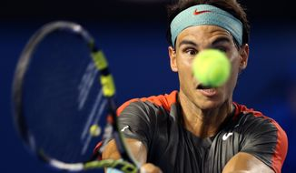 Rafael Nadal of Spain makes a backhand return to Bernard Tomic of Australia during their first round match at the Australian Open tennis championship in Melbourne, Australia, Tuesday, Jan. 14, 2014.(AP Photo/Rick Rycroft)