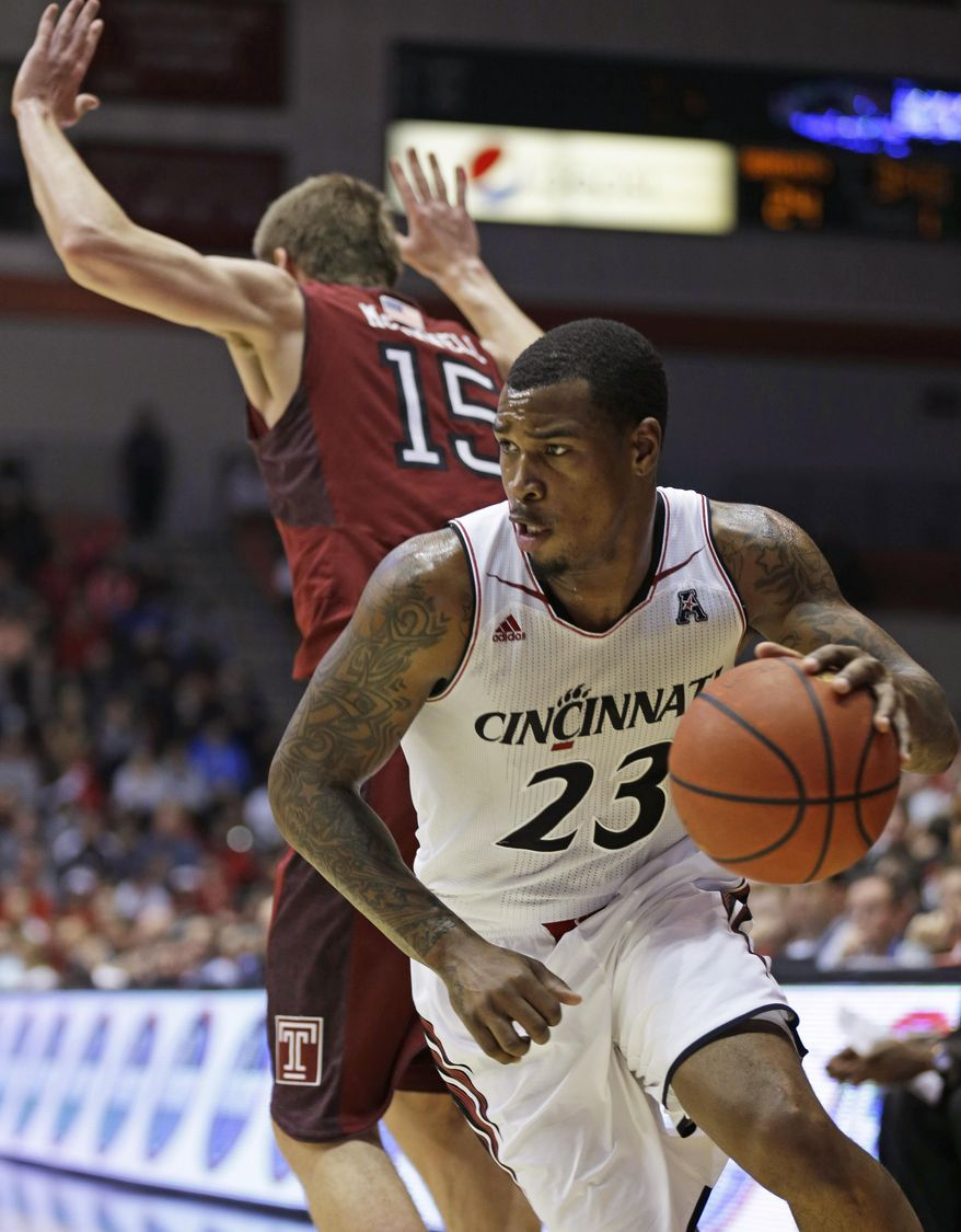 Cincinnati guard Sean Kilpatrick (23) drives around Temple forward Jimmy McDonnell (15) during the first half of an NCAA college basketball game, Tuesday, Jan. 14, 2014, in Cincinnati. (AP Photo/Al Behrman)