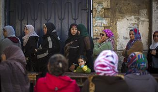 Egyptian women lines up to vote in the country's constitutional referendum in Cairo, Egypt, Tuesday, Jan. 14, 2014.  Upbeat and resentful of the Muslim Brotherhood, Egyptians voted Tuesday on a new constitution in a referendum that will pave the way for a likely presidential run by the nation's top general months after he ousted Islamist President Mohammed Morsi.(AP Photo/Khalil Hamra)