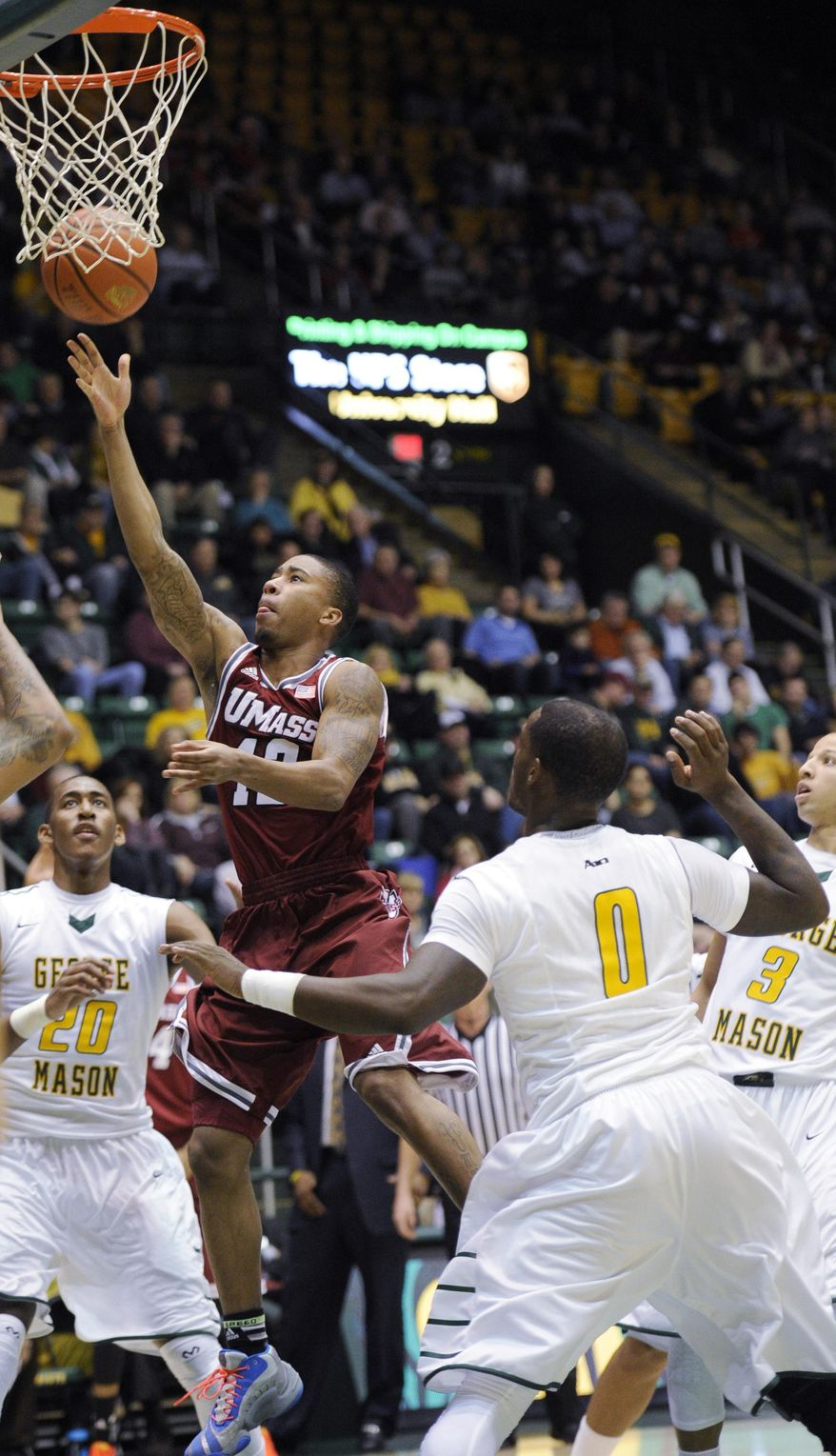 Massachusetts guard Trey Davis (12) goes to the basket against George Mason forward Jalen Jenkins (20) and Bryon Allen (0) during the first half of an NCAA college basketball game, Wednesday, Jan. 15, 2014, in Fairfax, Va. (AP Photo/Nick Wass)