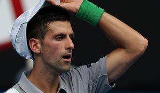 Novak Djokovic of Serbia adjusts his cap during his second round match against Leonardo Mayer of Argentina at the Australian Open tennis championship in Melbourne, Australia, Wednesday, Jan. 15, 2014.(AP Photo/Aaron Favila)