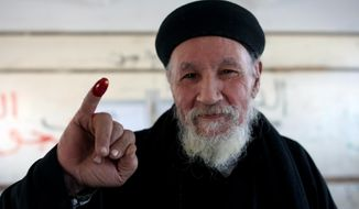 """Father Antonious shows his inked finger after casting his ballot in a constitutional referendum inside a polling station in Dalga village of Minya, Egypt, Wednesday, Jan. 15, 2014. He is one of the priests of the Virgin Mary and St. Abraam Monastery that was looted and burned by supporters of ousted Islamist President Mohammed Morsi in August. Through violence or intimidation, Islamists in villages like this one used violence or intimidation to stop Christians from voting """"no"""" to a 2012 constitution that had paved the way for the creation of an Islamic state. This time around, no one is stopping the  Christians and they are voting """"yes"""" on a new charter that criminalizes discrimination and instructs the next legislature to ease restrictions on building churches. (AP Photo/Roger Anis, El Shorouk Newspaper) EGYPT OUT"""