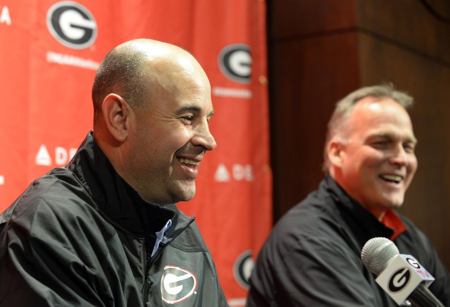 Jeremy Pruitt, left, is introduced as Georgia's new defensive coordinator by head football coach Mark Richt during an NCAA college football news conference on Wednesday, Jan. 15, 2014, in Athens, Ga. The former Florida State defensive coordinator, who helped lead the Seminoles to the 2013 BCS championship, said he would build relationships with Bulldog players to build their trust. (AP Photo/David Tulis)