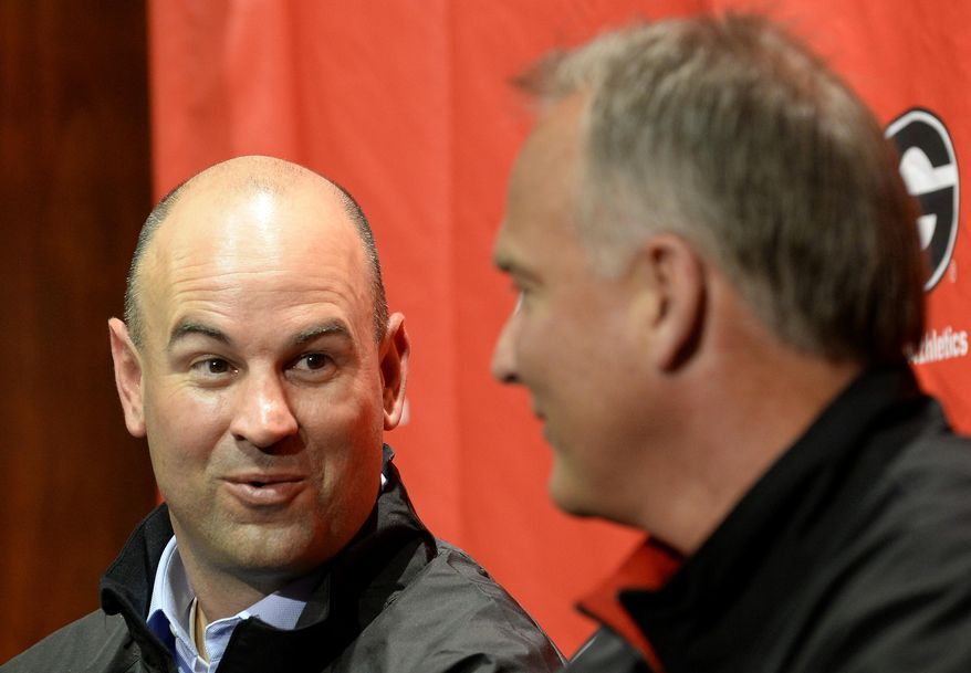 Jeremy Pruitt, left, is introduced as Georgia's new defensive coordinator by head football coach Mark Richt, right, during an NCAA college football news conference on Wednesday, Jan. 15, 2014, in Athens, Ga. The former Florida State defensive coordinator, who helped lead the Seminoles to the 2013 BCS championship, said he would build relationships with Bulldog players to build their trust. (AP Photo/David Tulis)