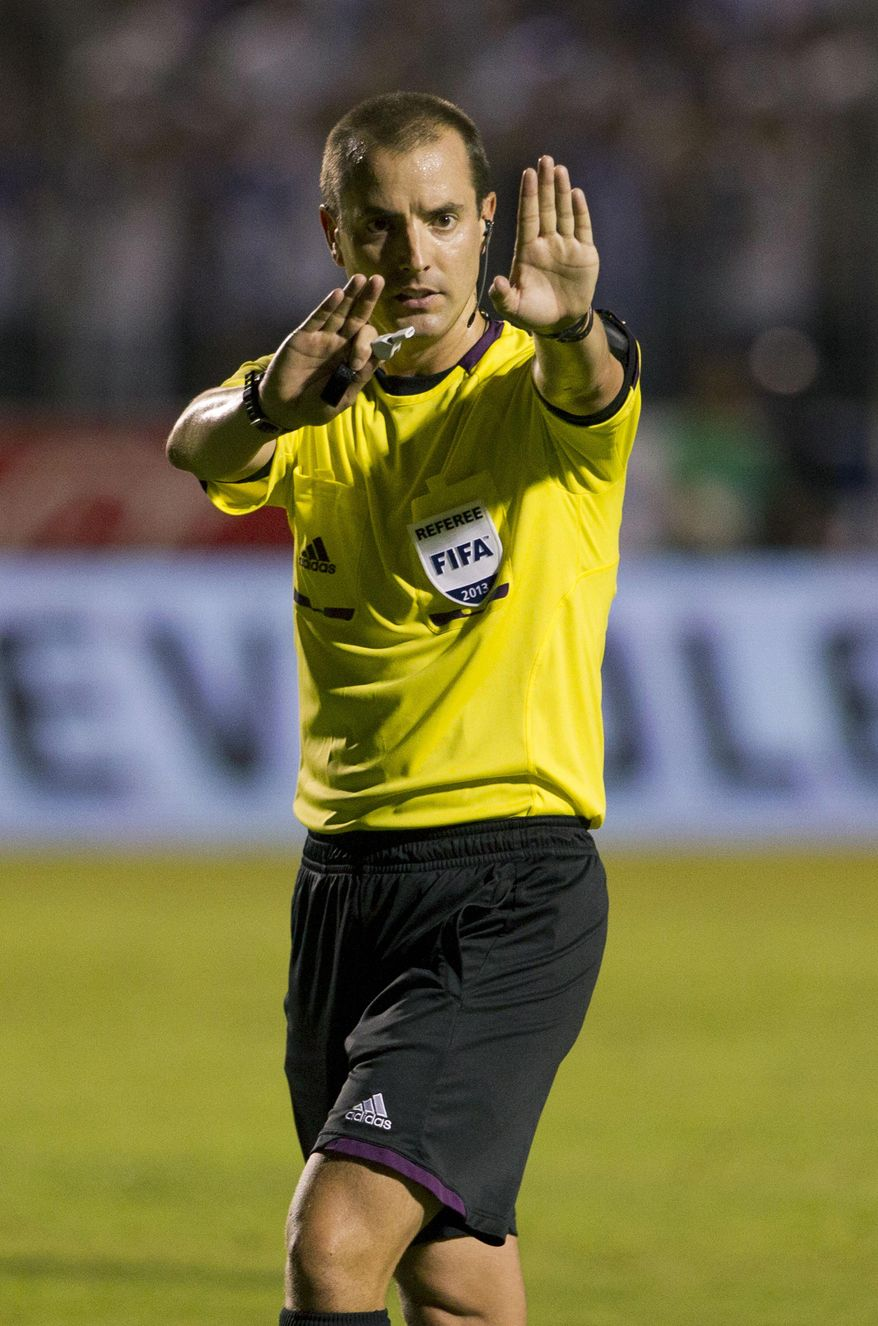 FILE - In this Tuesday Sept. 10, 2013 file photo, referee Mark Geiger signals a call at a 2014 World Cup qualifier soccer match between Honduras and Panama in Tegucigalpa, Honduras.  FIFA selected referee Mark Geiger on Wednesday Jan. 15, 2014, as one of the 25 who will officiate at the 2014 World Cup soccer tournament in Brazil. (AP Photo/Moises Castillo, File)