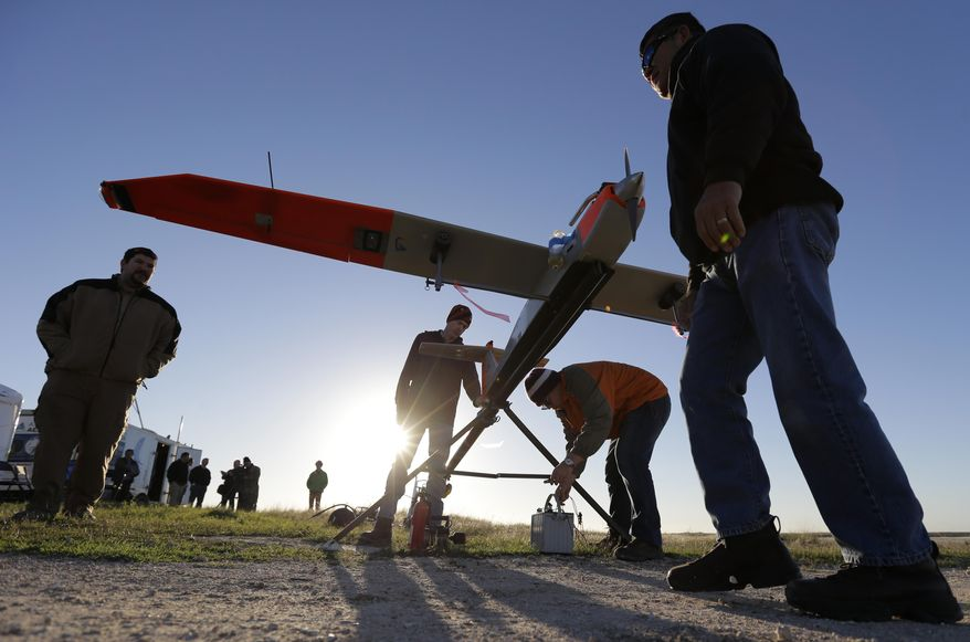 Texas A&M Corpus Christi researchers prepare a unmanned aircraft system for testing at a ranch near Sarita, Texas,  Wednesday, Jan. 15, 2014. The drone weighs about 85 pounds and has a wing span of almost 13 feet. (AP Photo/Eric Gay)