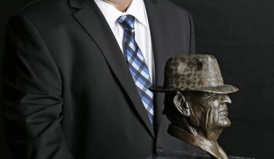 "Rice coach David Bailiff, finalist for the Paul ""Bear"" Bryant college coach of the year award, poses with the trophy Wednesday, Jan. 15, 2014, in Houston. (AP Photo/Pat Sullivan)"