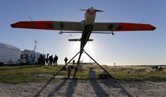 ** FILE ** Researchers prepare an unmanned aircraft system for testing at a ranch near Sarita, Texas,  Jan. 15, 2014. The drone used by Texas A&M researchers weighs about 85 pounds and has a wing span of almost 13 feet. (AP Photo/Eric Gay)