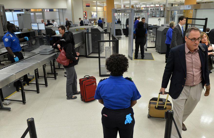 TSA agents man the checkpoint for pre-cleared passengers at Hartsfield-Jackson Atlanta International Airport on Wednesday, Jan. 15, 2014 in Atlanta. (AP Photo/Atlanta Journal-Constitution, Kent D. Johnson) ** FILE **