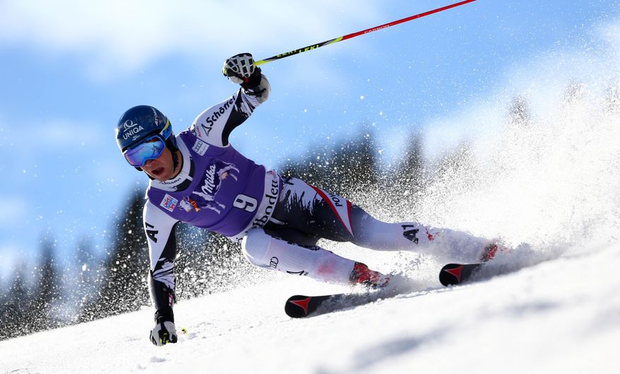 Banjamin Raich, of Austria, speeds down the course during an alpine ski, men's World Cup giant slalom in Adelboden, Switzerland, Saturday, Jan. 11, 2014. (AP Photo/Giovanni Auletta)