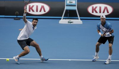 Australian players Pat Rafter, left, and Lleyton Hewitt play against Eric Butorac of the U.S and Klaasen Raven of South Africa in a first round doubles match at the Australian Open tennis championship in Melbourne, Australia, Wednesday, Jan. 15, 2014.(AP Photo/Rick Rycroft)