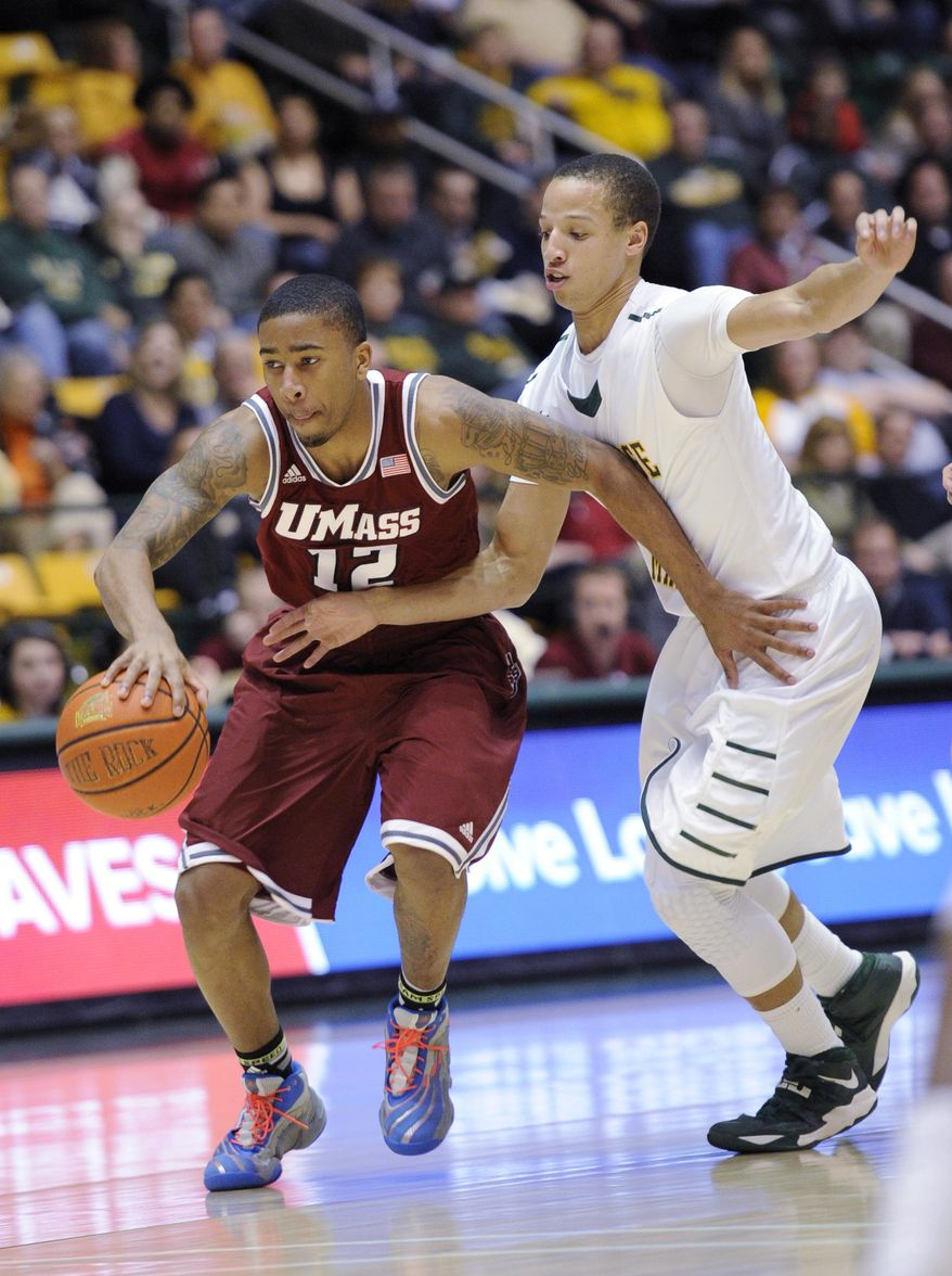 Massachusetts guard Trey Davis (12) dribbles the ball against George Mason guard Patrick Holloway, right, during the first half of an NCAA college basketball game, Wednesday, Jan. 15, 2014, in Fairfax, Va. (AP Photo/Nick Wass)