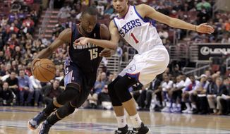 Charlotte Bobcats' Kemba Walker (15) drives against Philadelphia 76ers' Michael Carter-Williams (1) in the first half of an NBA basketball game, Wednesday, Jan. 15, 2014 in Philadelphia. (AP Photo/H. Rumph Jr.)