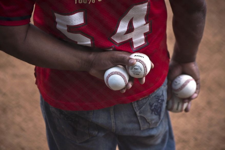 A man holds extra baseballs on the sidelines of an exhibition game between last year's college championship team from the University of Tampa and a Cuban youth squad in Havana, Cuba, Wednesday, Jan. 15, 2014. For one day at least, the heated rhetoric that often characterizes the divide between Havana and Washington was set aside in favor of an umpire's strike calls and the crack of the bat. (AP Photo/Ramon Espinosa)