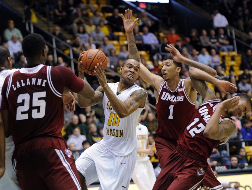 George Mason guard Sherrod Wright (10) looks to pass against Massachusetts forward/center Cady Lalanne (25), Maxie Esho (1) and Trey Davis (12) during the second half of an NCAA college basketball game, Wednesday, Jan. 15, 2014, in Fairfax, Va. Massachusetts won 88-87. (AP Photo/Nick Wass)