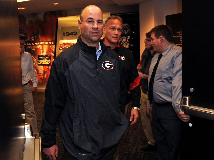 Georgia's new defensive coordinator Jeremy Pruitt, left, is escorted into an NCAA college football news conference by head football coach Mark Richt on Wednesday, Jan. 15, 2014, in Athens, Ga. The former Florida State defensive coordinator, who helped lead the Seminoles to the 2013 BCS championship, said he would build relationships with Bulldog players to build their trust. (AP Photo/David Tulis)