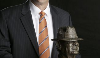 "Auburn coach Gus Malzhan, a finalist for the Paul ""Bear"" Bryant college coach of the year award, poses with the trophy Wednesday, Jan. 15, 2014, in Houston. (AP Photo/Pat Sullivan)"