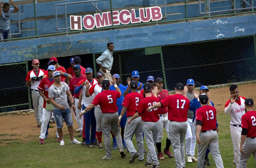 Baseball players from the University of Tampa, left, greet players from the Cuban youth squad at the end of their exhibition game in Havana, Cuba, Wednesday, Jan. 15, 2014. The visitors scraped out a hard-fought win, but the encounter was more about bridging the vast gulf between these neighboring nations that disagree on just about everything except their shared love of the game. (AP Photo/Ramon Espinosa)