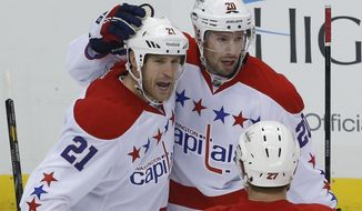 Washington Capitals' Brooks Laich (21) celebrates his goal with Troy Brouwer (20) after scoring in the first period of an NHL hockey game against the Pittsburgh Penguins in Pittsburgh, Wednesday, Jan. 15, 2014. (AP Photo/Gene J. Puskar)
