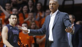 TCU coach Trent Johnson gestures to an official during the first half of TCU's NCAA college basketball game against Oklahoma State in Stillwater, Okla., Wednesday, Jan. 15, 2014. (AP Photo/Sue Ogrocki)