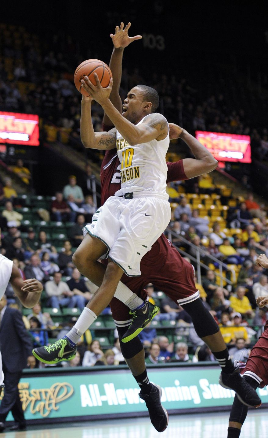 George Mason guard Sherrod Wright (10) gets fouled by Massachusetts forward/center Cady Lalanne, back, as he goes to the basket during the second half of an NCAA college basketball game, Wednesday, Jan. 15, 2014, in Fairfax, Va. Massachusetts won 88-87. (AP Photo/Nick Wass)