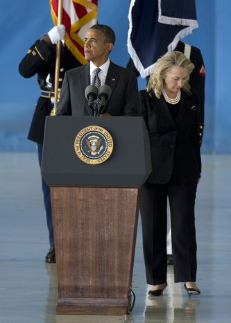**FILE** President Obama stands at the podium to speak as Secretary of State Hillary Rodham Clinton steps aside during the Transfer of Remains Ceremony at Andrews Air Force Base, Md., on Sept. 14, 2012, marking the return to the United States of the remains of the four Americans killed this week in Benghazi, Libya. (Associated Press)