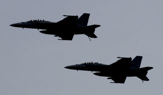 A picture taken Monday, Feb. 13, 2012 shows U.S. F-18 fighter jets flying over the Nimitz-class aircraft carrier USS Abraham Lincoln (CVN 72) during fly exercises in the Persian Gulf.  (AP Photo/Hassan Ammar) ** FILE **