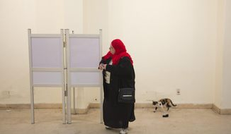 An Egyptian woman fills her ballot before casting in a two-day constitutional referendum in Cairo, Egypt, Wednesday, Jan. 15, 2014. Egyptians voted on the second, final day of a key referendum on a new constitution seen as a precursor to the country's presidential elections, in which it is largely expected that El-Sissi will run. (AP Photo/Hiro Komae)