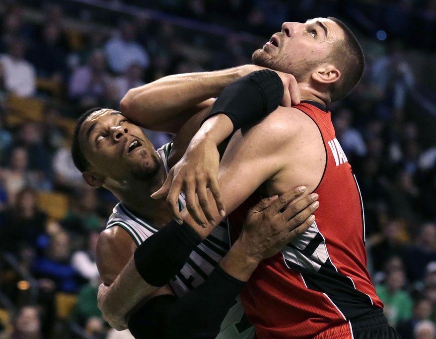 Boston Celtics forward Jared Sullinger, left, tangles with Toronto Raptors center Jonas Valanciunas on a rebound during the first quarter of an NBA basketball game in Boston, Wednesday, Jan. 15, 2014. (AP Photo/Charles Krupa)