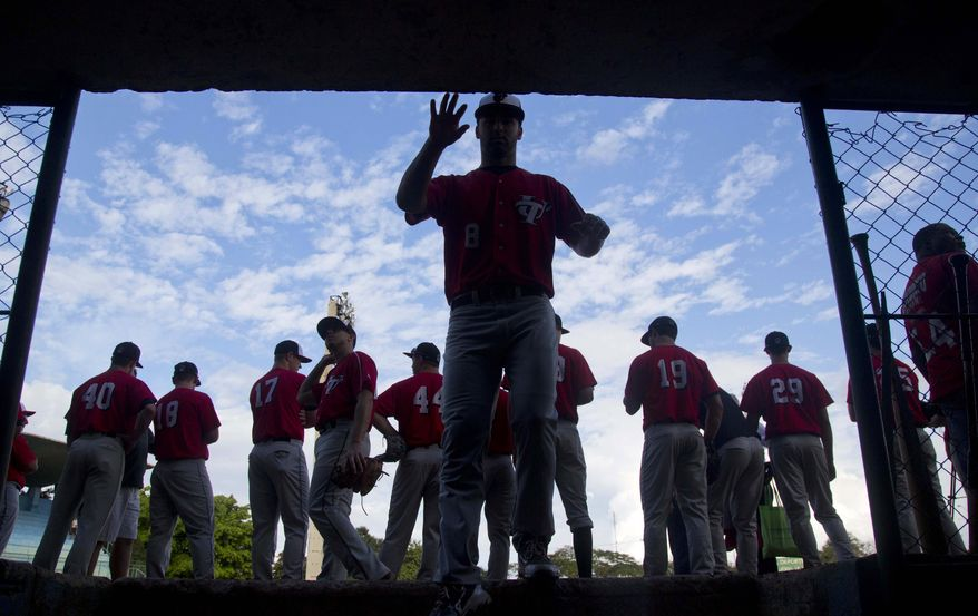A baseball player from the University of Tampa reaches for the wall as he enters the dugout before the start of a game with Cuba's youth squad in Havana, Cuba, Wednesday, Jan. 15, 2014. Balls and strikes, not politics, ruled the day Wednesday at a baseball diamond in Havana, as last year's college championship team from the University of Tampa played an exhibition game against a Cuban youth squad. (AP Photo/Ramon Espinosa)
