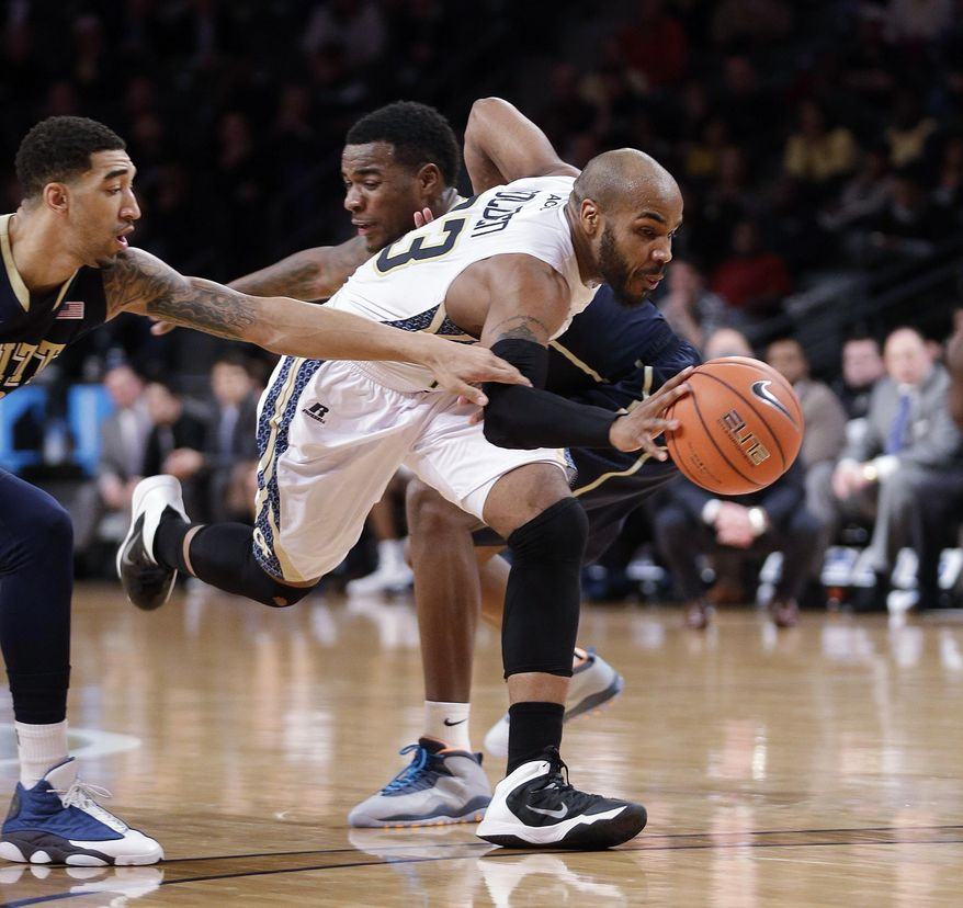 Georgia Tech guard Trae Golden (23) drives between Pittsburgh's Michael Young (2) left, and Cameron Wright (3) in the second half of an NCAA college basketball game Tuesday, Jan. 14, 2014, in Atlanta. (AP Photo/John Bazemore)
