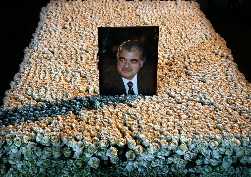 A portrait of slain Lebanese Prime Minister Rafik Hariri sits on his grave which is covered by flowers in downtown Beirut, Lebanon, Wednesday, Jan. 15, 2014. Nearly nine years after the truck bomb assassination of former Lebanese Prime Minister Rafik Hariri shook the Middle East and awakened the seeds of Sunni-Shiite hatreds, an international tribunal begins the long awaited trial of four Hezbollah suspects Thursday. The men have not been arrested, and the Hague-based court will try them in absentia in the first such trial since World War II. (AP Photo/Hussein Malla)