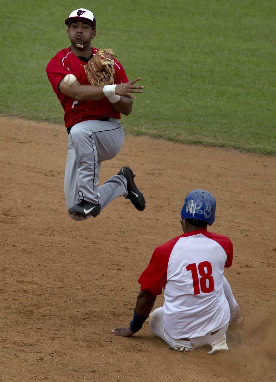 A player from the University of Tampa, left, outs a player from a Cuban youth team at second and throws to first during an exhibition game in Havana, Cuba, Wednesday, Jan. 15, 2014.  Cultural exchanges between Cuba and the U.S. have become increasingly common in recent years. President Barack Obama's administration has restored so-called people-to-people tours, resulting in tens of thousands of Americans visiting the island each year legally.  (AP Photo/Ramon Espinosa)