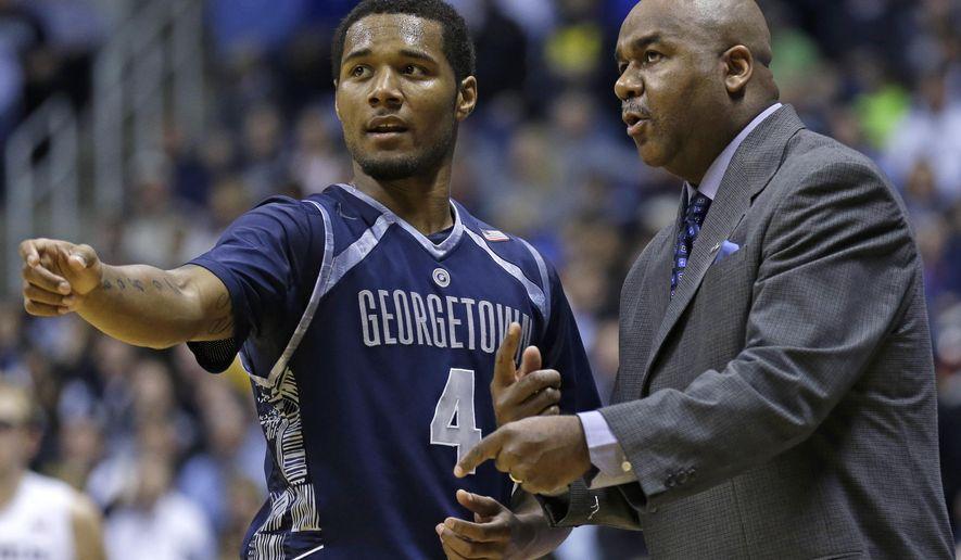 Georgetown head coach John Thompson III, right, talks with guard D'Vauntes Smith-Rivera (4) in the second half of an NCAA college basketball game against Xavier, Wednesday, Jan. 15, 2014, in Cincinnati. Xavier won 80-67. (AP Photo/Al Behrman)