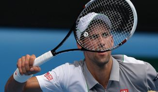 Novak Djokovic of Serbia makes a forehand return to Leonardo Mayer of Argentina during their second round match at the Australian Open tennis championship in Melbourne, Australia, Wednesday, Jan. 15, 2014.(AP Photo/Aaron Favila)