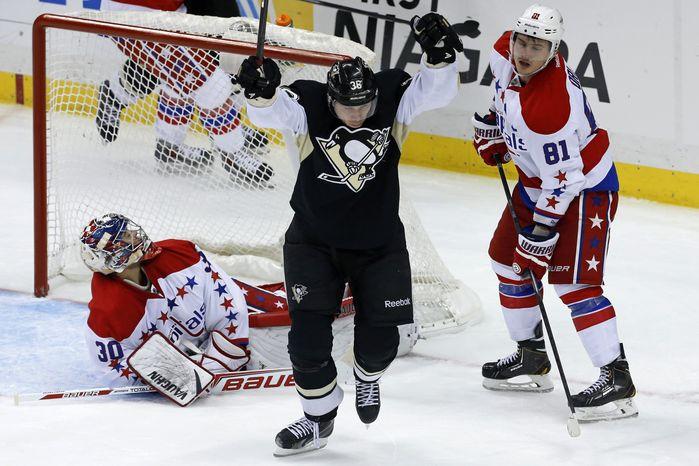 Pittsburgh Penguins' Jussi Jokinen (36) celebrates his goal between Washington Capitals goalie Michal Neuvirth (30) and Dmitry Orlov (81) in the third period of an NHL hockey game in Pittsburgh, Wednesday, Jan. 15, 2014. The Penguins won 4-3. (AP Photo/Gene J. Puskar)