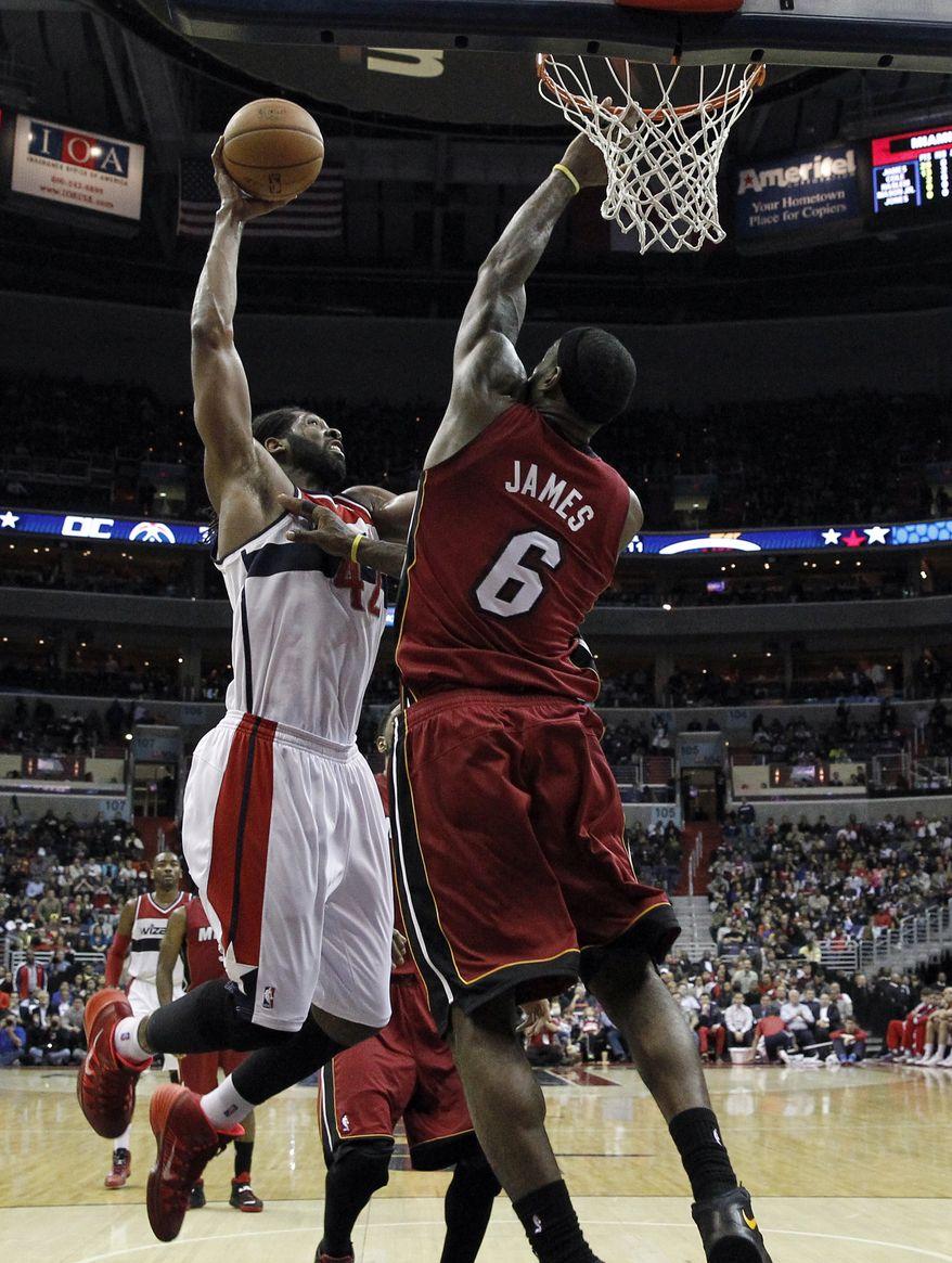 Washington Wizards forward Nene (42), from Brazil, dunks the ball over Miami Heat forward LeBron James (6) in the second half of an NBA basketball game on Wednesday, Jan. 15, 2014, in Washington. The Wizards won 114-97. (AP Photo/Alex Brandon)