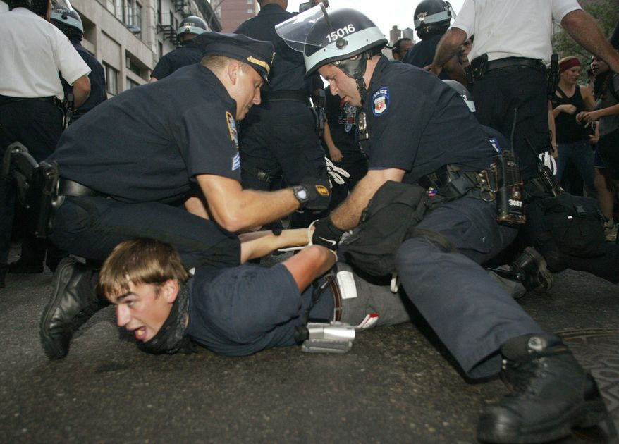 FILE - This Aug. 31, 2004 file photo shows a protester being arrested by  New York City Police officers during the Republican National Convention in New York.  New York City agreed Jan. 15, 2014, to pay $18 million to settle dozens of lawsuits filed by protesters, journalists and bystanders who said they were wrongly arrested at the 2004 Republican National Convention, lawyers said Wednesday. (AP Photo/Mary Altaffer, File)