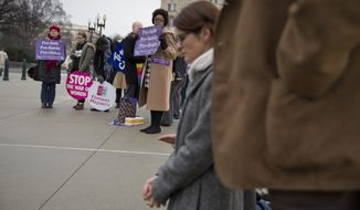 Pro-choice demonstrators (left) watch as a group of anti-abortion demonstrators pray on the steps of the Supreme Court when the court heard arguments about a protest-free zone outside Massachusetts abortion clinics. The high court struck down the law in 2014. (Associated Press)