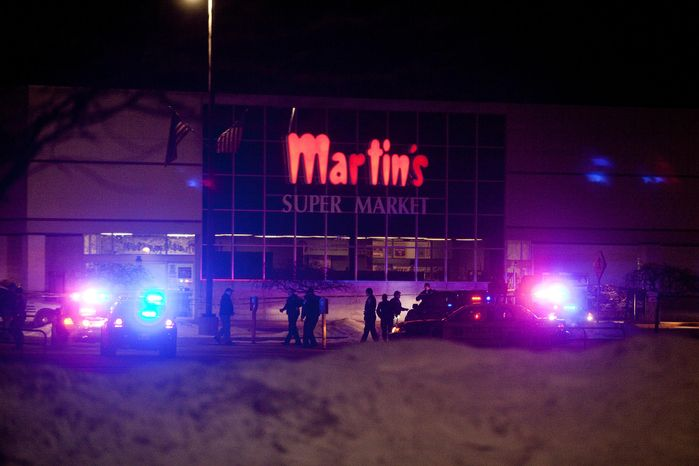 Elkhart Police, the Elkhart Fire Department, Indiana State Police and emergency personnel respond to reports of a shooting inside Martin's Supermarket in Elkhart, Ind., about 10:30 p.m. Wednesday, Jan. 15, 2014. Three people, including the gunman, died Wednesday night after a shooting at an Elkhart grocery store. (AP Photo/Truth, Larry Tebo)