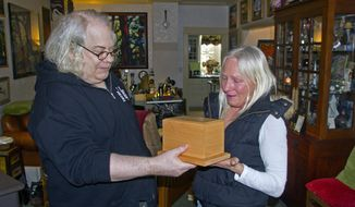 Gerry Sperry, of Puyallup, presents Kim Johnson with a box containing the ashes of her 165-pound rottweiler, Onyx, Thursday, Jan. 15, 2014 at Sperry's home in Puyallup, Wash. Sperry purchased the box, which was stolen from Johnson a year ago, for $2.99 from a Puyallup Goodwill on Dec. 31. (AP Photo/The News Tribune, Larry Larue)