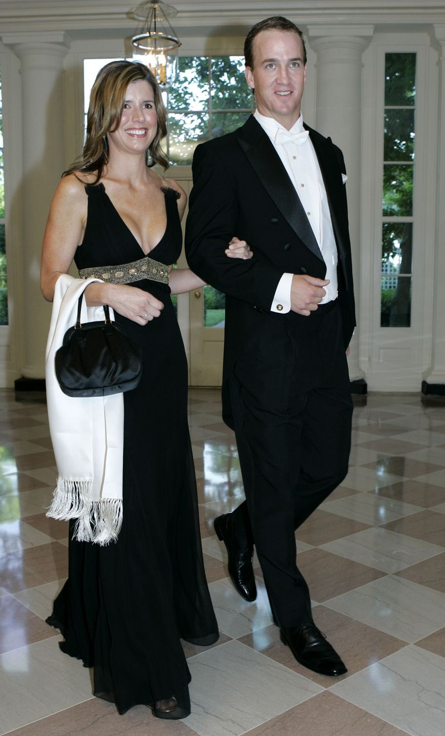 Indianapolis Colts quarterback Peyton Manning, right, and his wife Ashley walk through the Booksellers Area as they arrive for the State Dinner in honor of Queen Elizabeth II and her husband Prince Philip, Monday, May 7, 2007, at the White House in Washington. (AP Photo/Haraz N. Ghanbari)