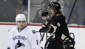 Anaheim Ducks' Teemu Selanne, right, of Finland, celebrates his goal as Vancouver Canucks' Chris Tanev looks on during the first period of an NHL hockey game on Wednesday, Jan. 15, 2014, in Anaheim, Calif. (AP Photo/Jae C. Hong)