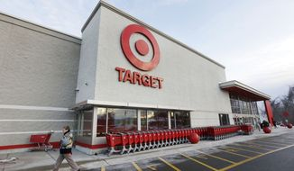 In this Dec. 19, 2013, file photo, a passer-by walks near an entrance to a Target retail store in Watertown, Mass. (AP Photo/Steven Senne, File) **FILE**