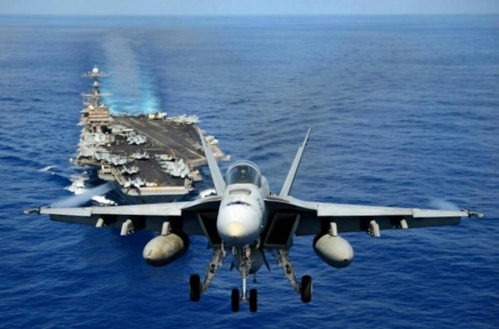 An F-18 Super Hornet flies ahead of the USS John C. Stennis while in the Pacific, 2013. (Image: U.S. Navy)