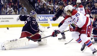 Columbus Blue Jackets' Sergei Bobrovsky, left, of Russia, makes a save against Washington Capitals' Jay Beagle, right, as Blue Jackets' Artem Anisimov, also of Russia, waits for a rebound during the first period of an NHL hockey game on Friday, Jan. 17, 2014, in Columbus, Ohio. The Blue Jackets won 5-1. (AP Photo/Jay LaPrete)