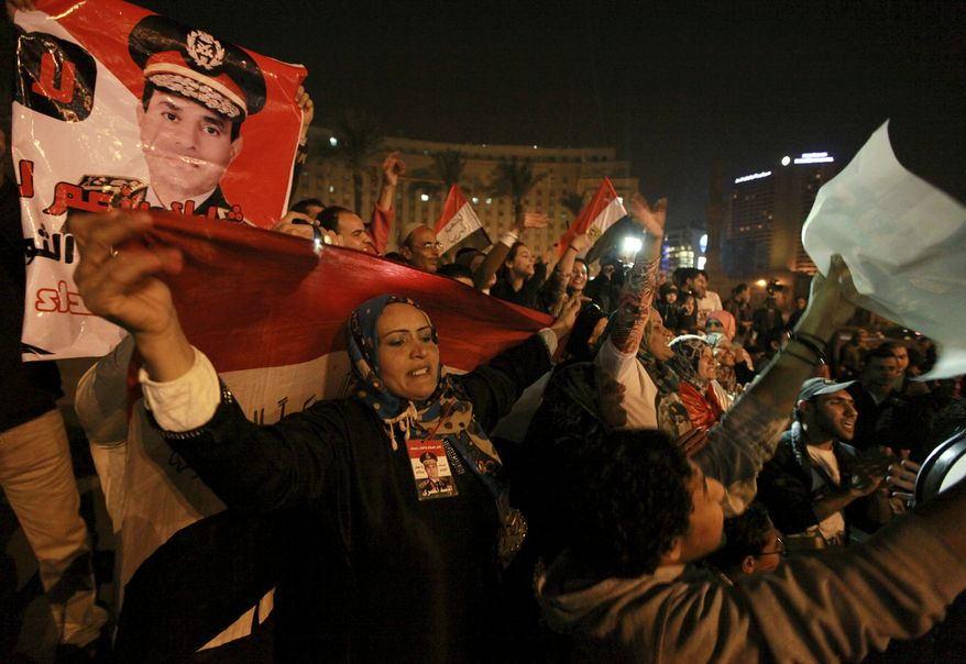 """Holding national flags and portraits of military chief  Gen. Abdel-Fattah el-Sissi, Egyptians celebrate the passage of a new constitution after 98.1 percent of voters supported Egypt's military-backed constitution in a two-day election, in Tahrir Square, Cairo, Egypt, Saturday, Jan. 18, 2014. In the lead up to the vote, police arrested those campaigning for a """"no"""" vote on the referendum, leaving little room for arguing against the document. (AP Photo/El Shorouk Newspaper, Sabry Khaled)  EGYPT OUT"""